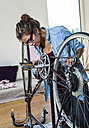 Young woman at home repairing her bicycle - UUF004697