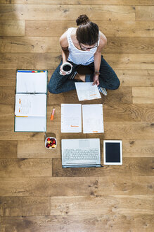 Student sitting on wooden floor surrounded by papers, laptop, digital tablet, file folder and fruit bowl - UUF004741