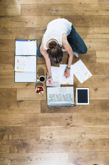 Student sitting on wooden floor surrounded by papers, laptop, digital tablet, file folder, coffee and fruit bowl - UUF004702