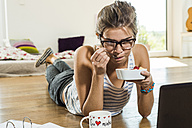 Young woman lying on wooden floor eating fruit from bowl - UUF004703
