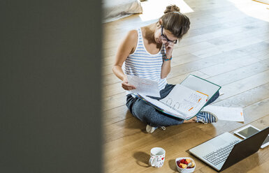 Young woman sitting on wooden floor with file folder and laptop - UUF004747