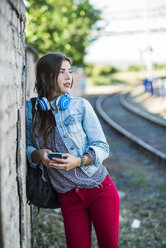 Brunette young woman with headphones and cell phone leaning against brick wall - UUF004723