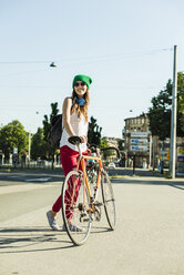 Smiling young woman with bicycle on pavement - UUF004728