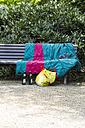 Germany, Baden-Baden, bench with sleeping bag, plastic bag and beer bottles - JUN000316