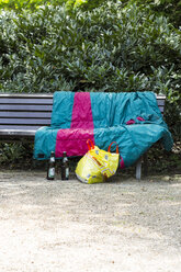 Germany, Baden-Baden, bench with sleeping bag, plastic bag and beer bottles - JUN000316