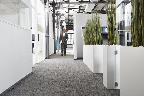 Smiling businessman walking in modern office - PDF000983