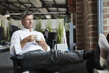 Businessman in office having a coffee beak - PDF001006