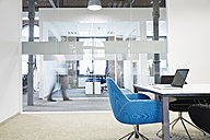 Conference room with blue chair and blurred businessman in the background - PDF001042
