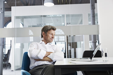 Businessman in conference room looking at laptop - PDF001013