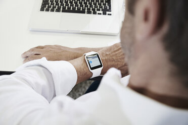Businessman in office looking at smartwatch - PDF001068