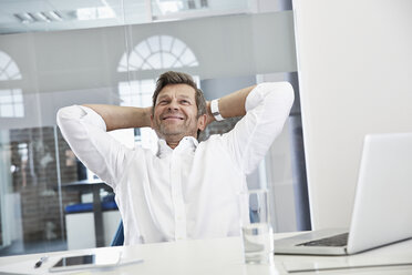 Portrait of smiling businessman in office relaxing - PDF001019
