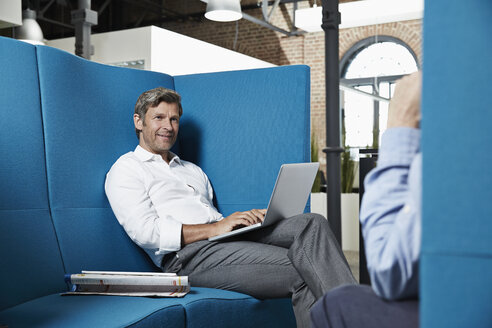 Businessman sitting in conversation pit in office looking at colleague - PDF001028