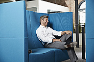 Smiling businessman sitting in conversation pit in office - PDF001031