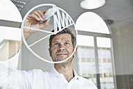Businessman drawing diagram on glass pane in office - PDF001043