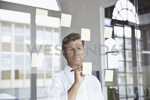 Businessman writing on sticky note on glass pane in office - PDF001046 - Philipp Dimitri/Westend61