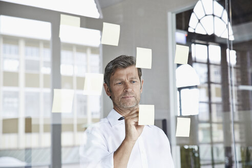 Businessman writing on sticky note on glass pane in office - PDF001046