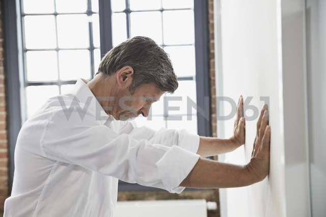 Frustated businessman in office leaning against a wall - PDF001049