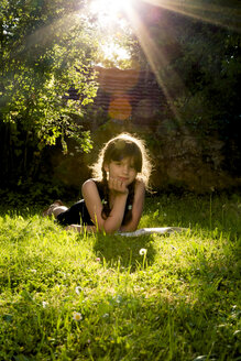 Portrait of girl lying on a meadow with a book - LVF003495