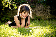 Girl lying on a meadow reading a book - LVF003497