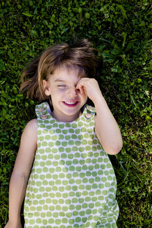 Smiling little girl with closed eyes lying on a meadow - LVF003502