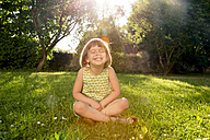 Little girl wearing cherries sitting on a meadow at backlight - LVF003505