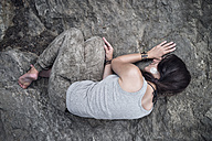 Woman lying huddled on rock - MW000087