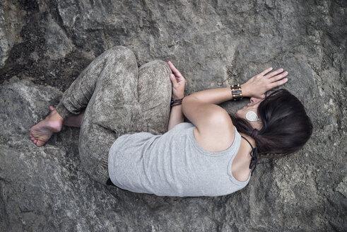 Woman lying huddled on rock - MW000087