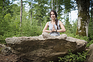 Woman sitting on rock in forest meditating - MW000088