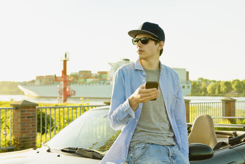 Teenager leaning at convertible car with smartphone - MSF004629