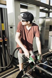 Teenager at gas station refuellng convertible car - MSF004630