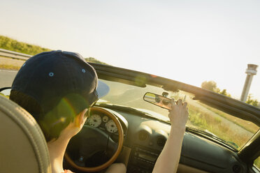 Teenager driving in a convertible car adjusting rear view mirror - MSF004633