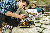 Young couple having a barbecue - UUF004759