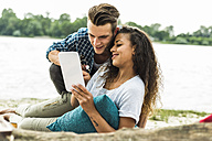 Smiling young couple with digital tablet outdoors - UUF004776