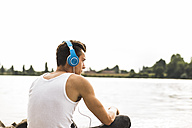 Young man by the riverside wearing headphones - UUF004782