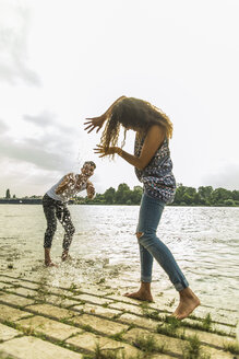 Playful young couple splashing with water by the riverside - UUF004795