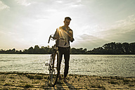 Young man with bicycle and cell phone by the riverside - UUF004816