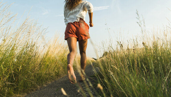 Young woman running on path in field - UUF004833