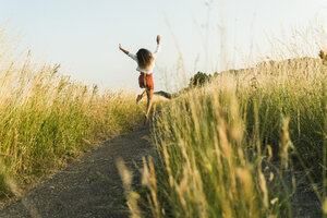 Enthusiastic young woman jumping on path in field - UUF004834
