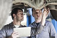 Two car mechanics at work in repair garage - ZEF005690