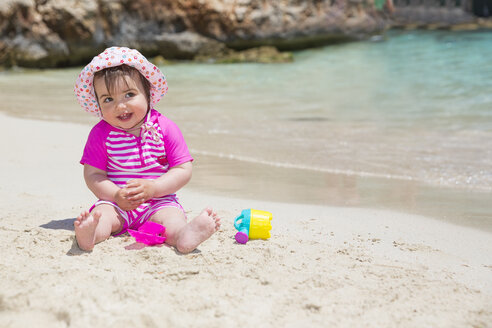 Spain, Baleares, Mallorca, baby girl playing on sandy beach - ROMF000047