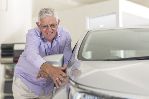 Senior man looking at a new car in showroom - ZEF006346