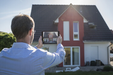 Man photographing his house with digital tablet - PAF001433