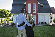 Happy couple standing arm in arm in the garden looking at their house - PAF001435