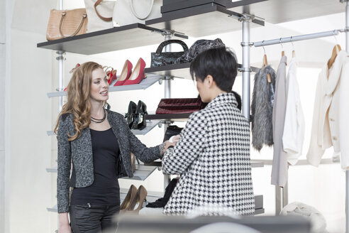 Shop assistant advising woman in a boutique - ZEF006695