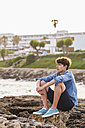 Greece, Rhodes, young man sitting at seafront looking at distance - WDF003144