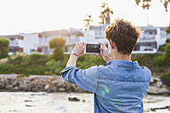 Greece, Rhodes, young man photographing with smartphone at seafront - WDF003149