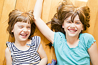 Portrait of two laughing sisters lying on wooden floor - LVF003516