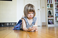 Little girl lying on wooden floor looking sceptical at smartphone - LVF003532