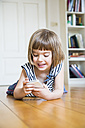 Portrait of smiling little girl lying on wooden floor with smartphone - LVF003526