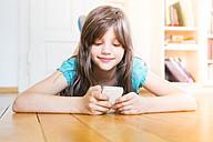Smiling girl lying on wooden floor using smartphone - LVF003529